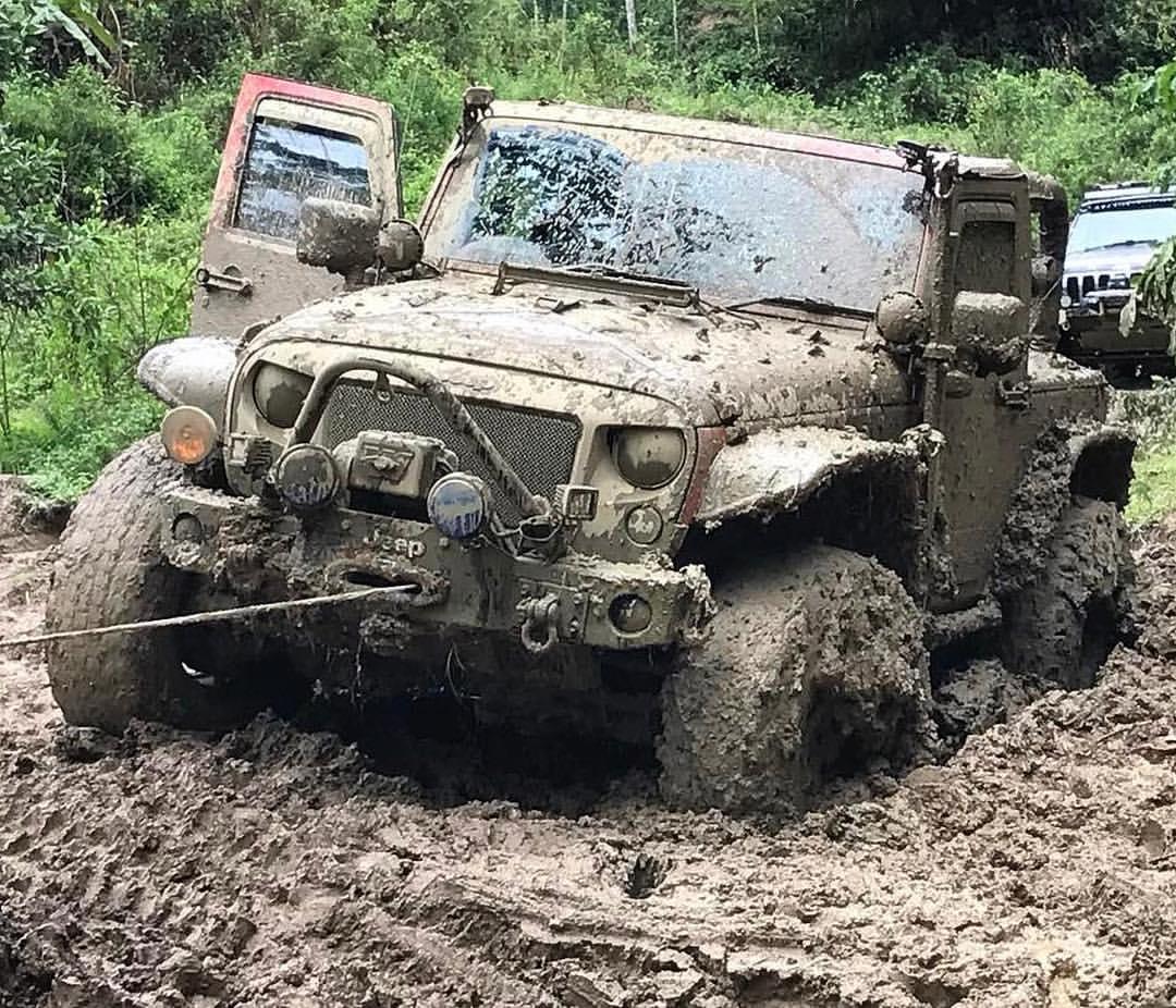 Ein Jeep zieht sich mit der Seilwinde aus dem Schlamm