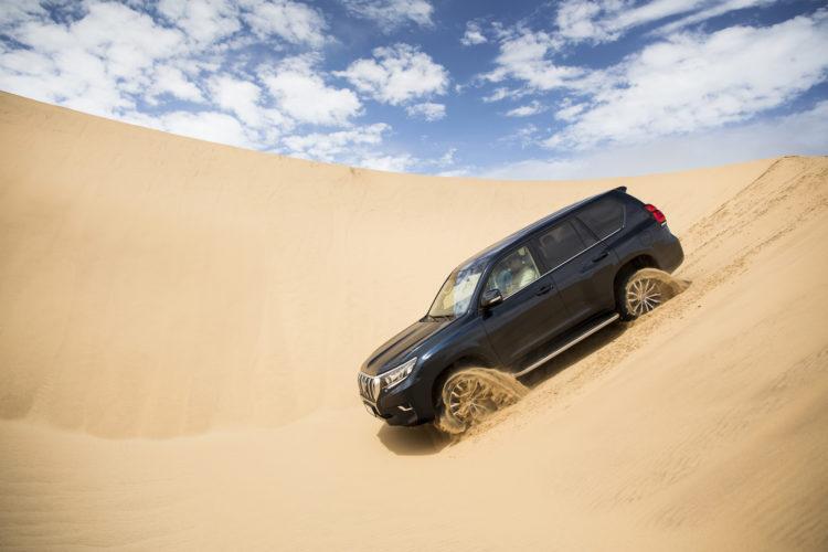 Toyota Land Cruiser gleitet über eine Sand-Dühne